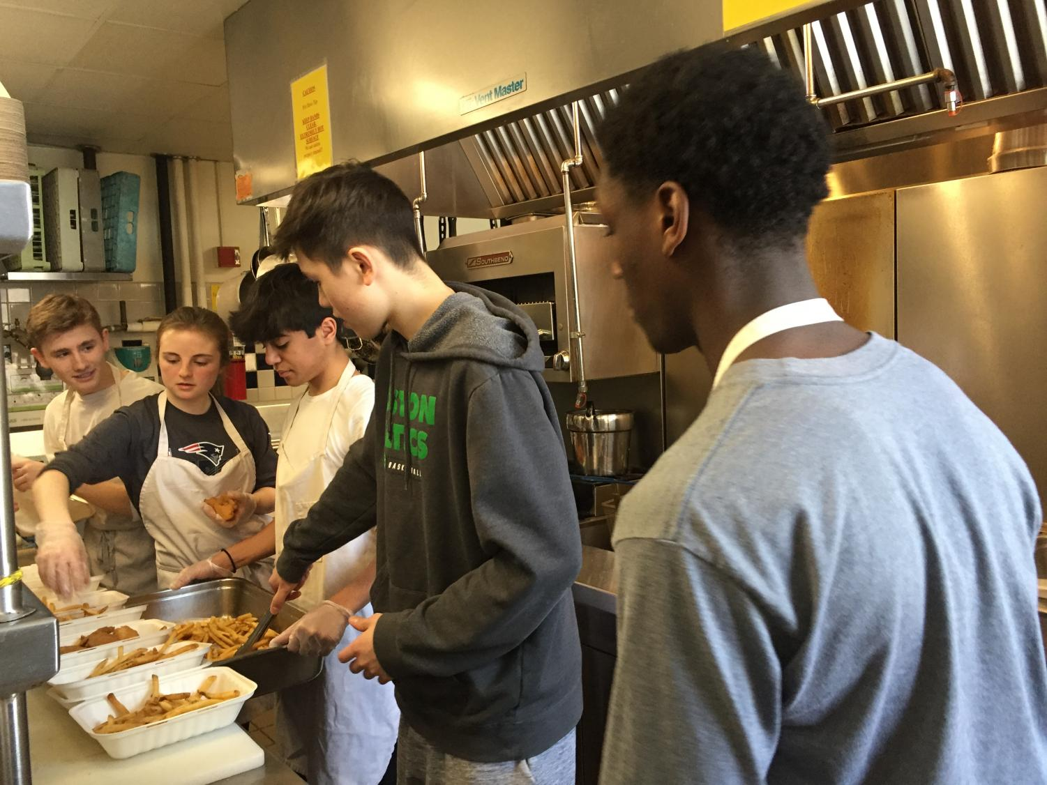Students prepare food behind the scenes in the Restaurant 108 kitchen.
