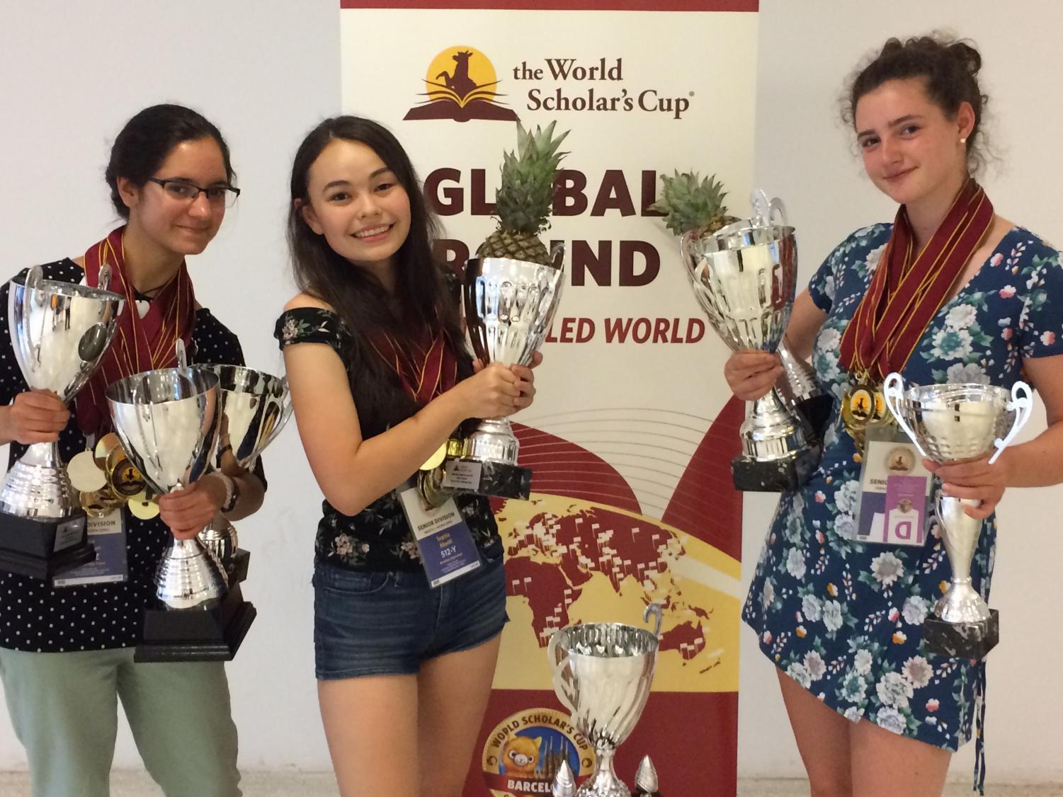 The World Scholars Cup club co-presidents and co-founders Sophia Maehl, Sophie Tsekov and Julia Riesman celebrate with trophies after winning the final round of the competition.