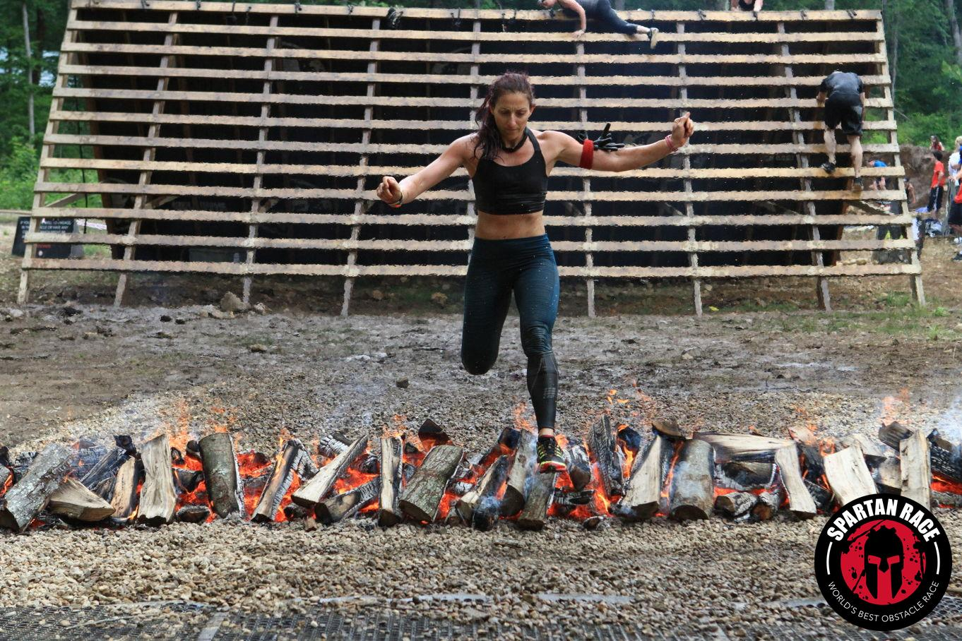 Steps to Success advisor Melissa Sirin jumps over a flaming bed of wood during a spartan race. According to Sirin, she loves this sport because it is constantly challenging her in new ways.