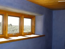 Window set in hand dyed plastered Straw Bale wall with Douglas Fir sill.