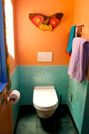Wall mounted toilet on glass tile wainscoting.