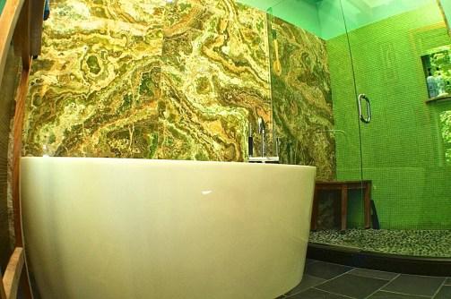 Vessel bath tub on charcol slate floor with green Onyx stone behind.