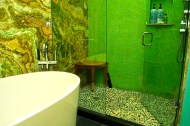 Vessel bath tub on charcol slate floor with green Onyx stone behind.