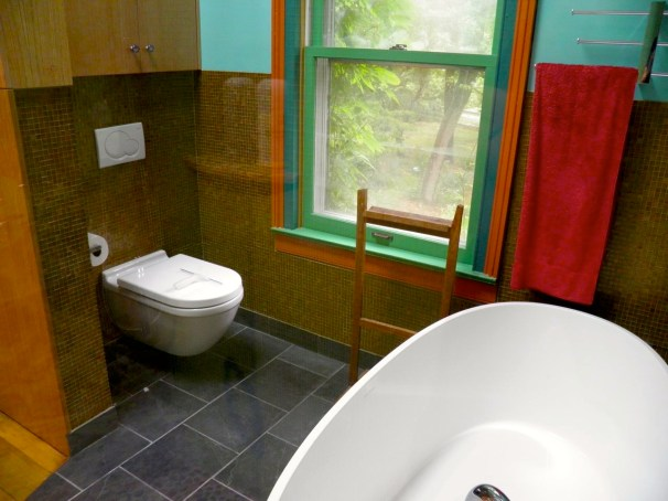 Wall mounted toilet on Brown colored Glass Tile wall.