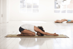 woman doing meditative yoga on a yoga mat in a white studio