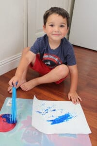 preschooler using recycled materials (bunch a balloons) to paint