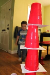toddler engineering a tower of red solo cups