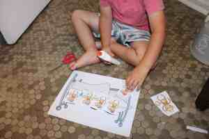 a toddler gluing 5 little monkeys onto a paper bed