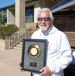 Perry poses with the gold record he received for producing a television theme song that sold nearly 3 million copies abroad.