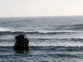 Shark cage diving crew waits for a break in the easterly inspired surf.