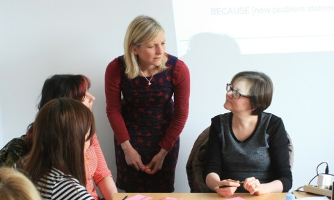 Workshop with a standing woman giving advice to three seated women