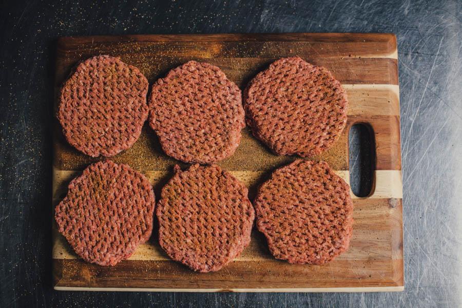 Burger patties sprinkled with Oakridge BBQ Santa Maria Seasoning
