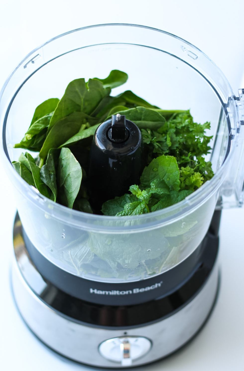 spinach and herbs in a food processor