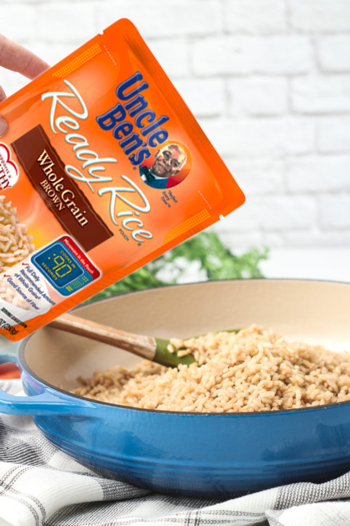 Pouring a bag of Uncle Bens Brown Rice into a skillet