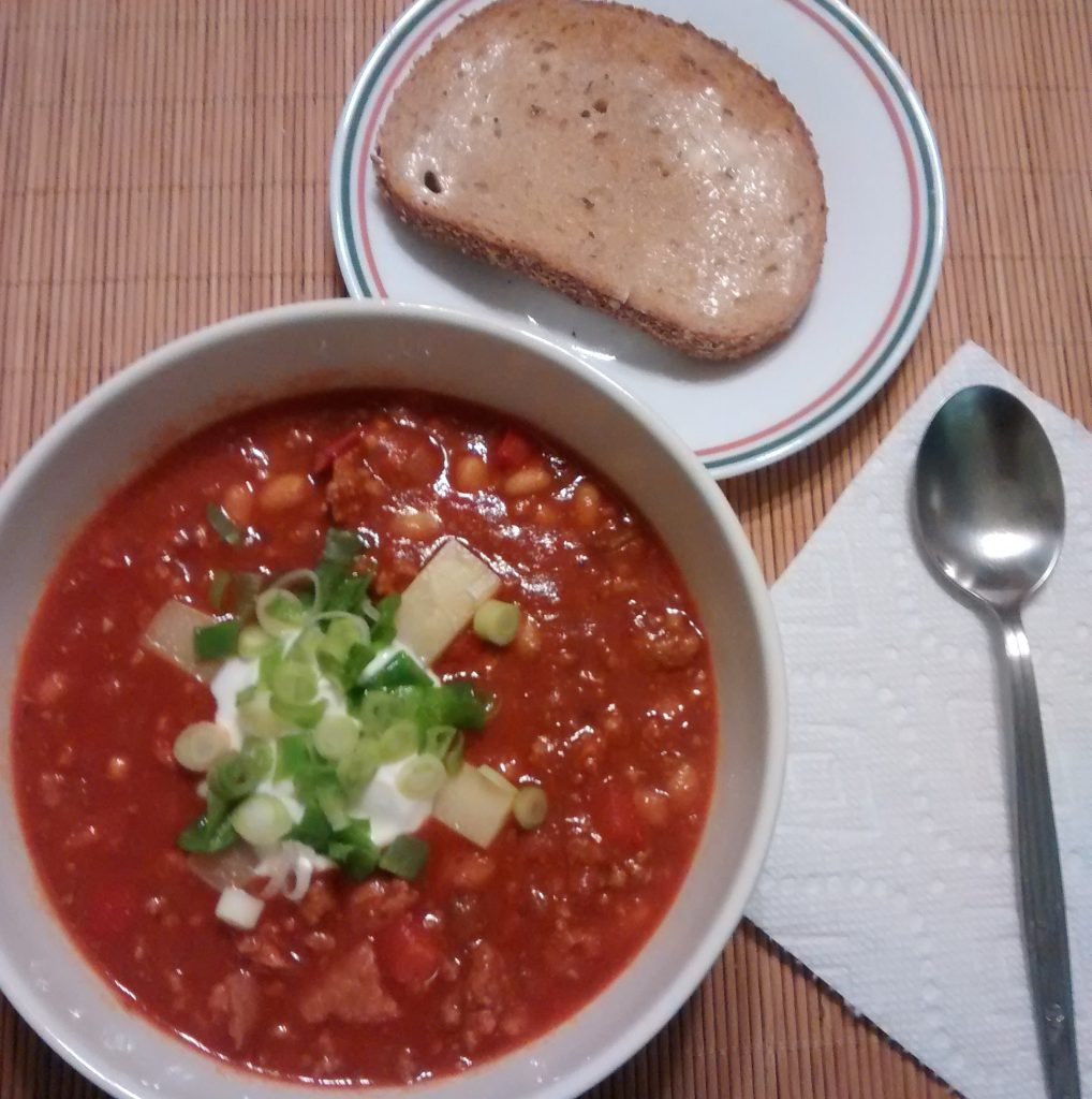 Chilli bowl with bread and spoon on a napkin