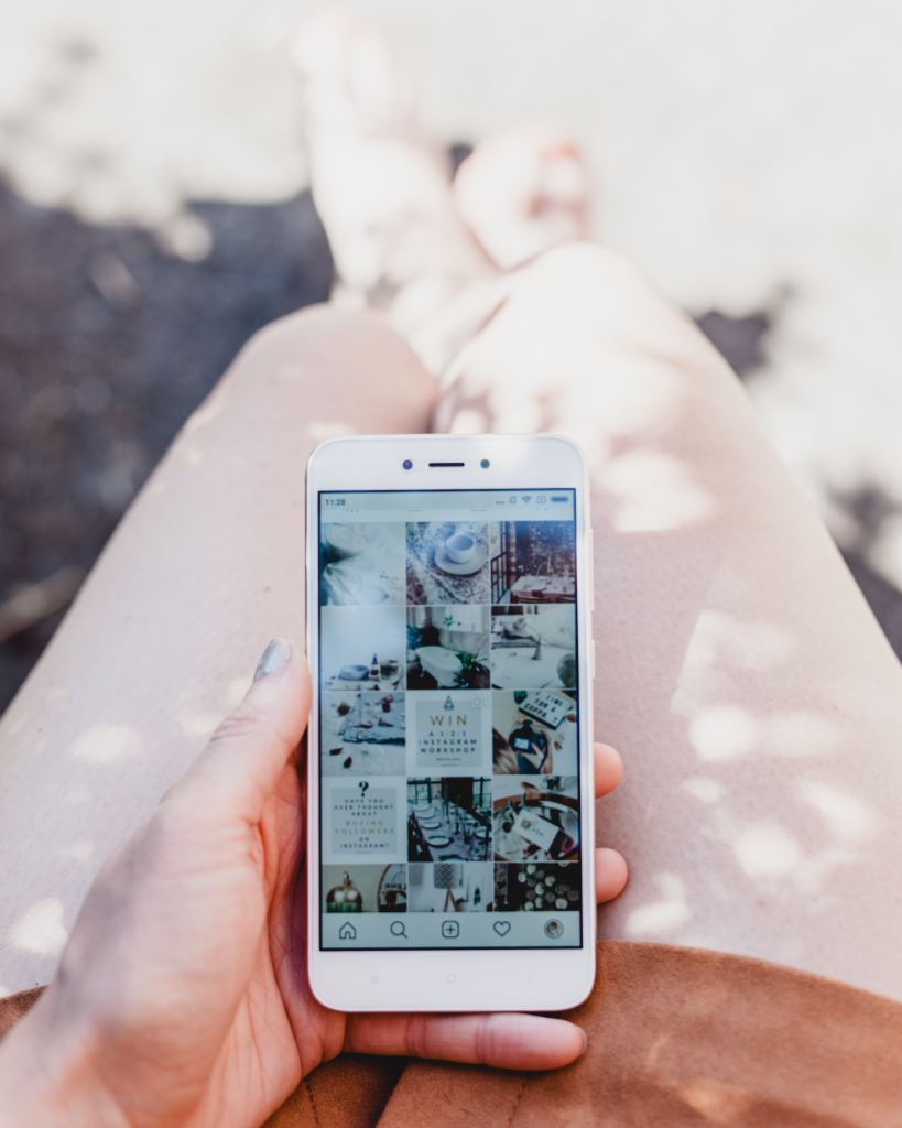 Photo by Georgia de Lotz on Unsplash holding phone looking at social media