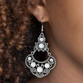 Glowing white beads and glittery white rhinestones are sprinkled along an ornate silver frame radiating with leafy filigree for a whimsical look. Earring attaches to a standard fishhook fitting. Sold as one pair of earrings.
