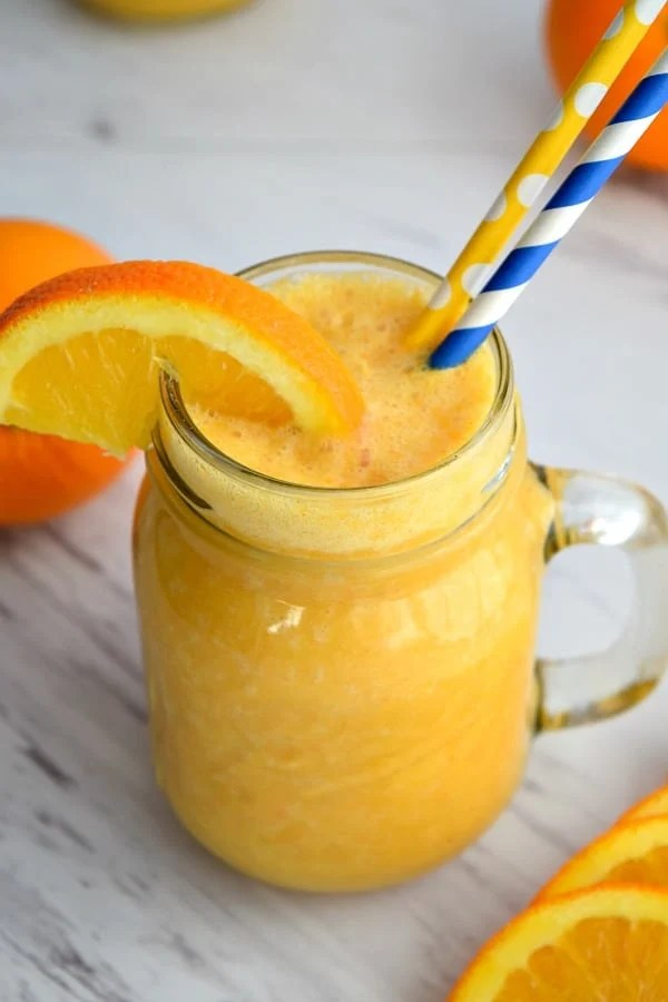 close up top view of orange ginger smoothie with an orange wedge