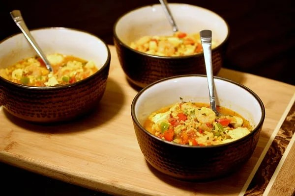 three bowls of chicken and shrimp paella on a table