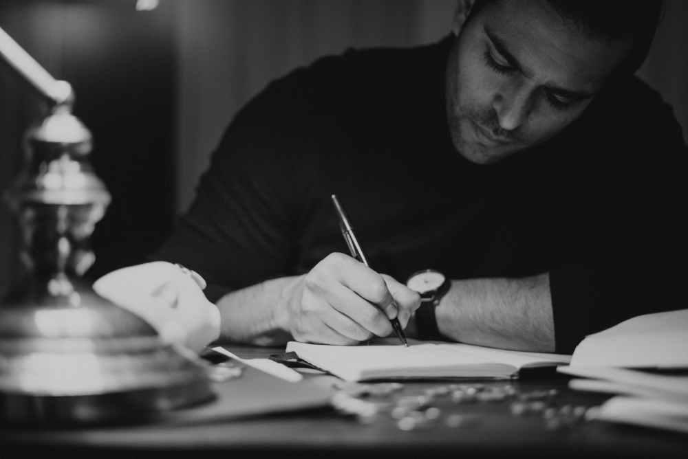 crop man taking notes in copybook in dark home office