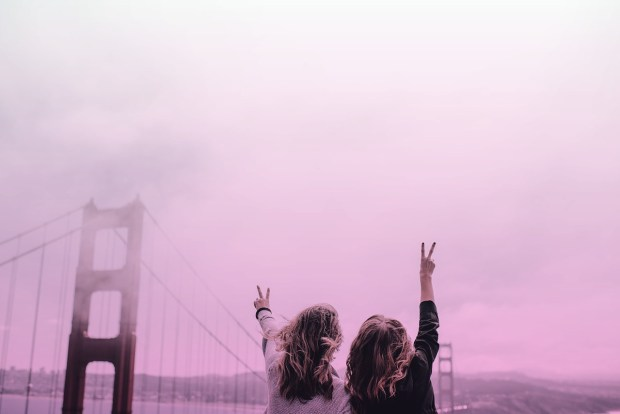 Women giving peace signs in front of Golden Gate Bridge
