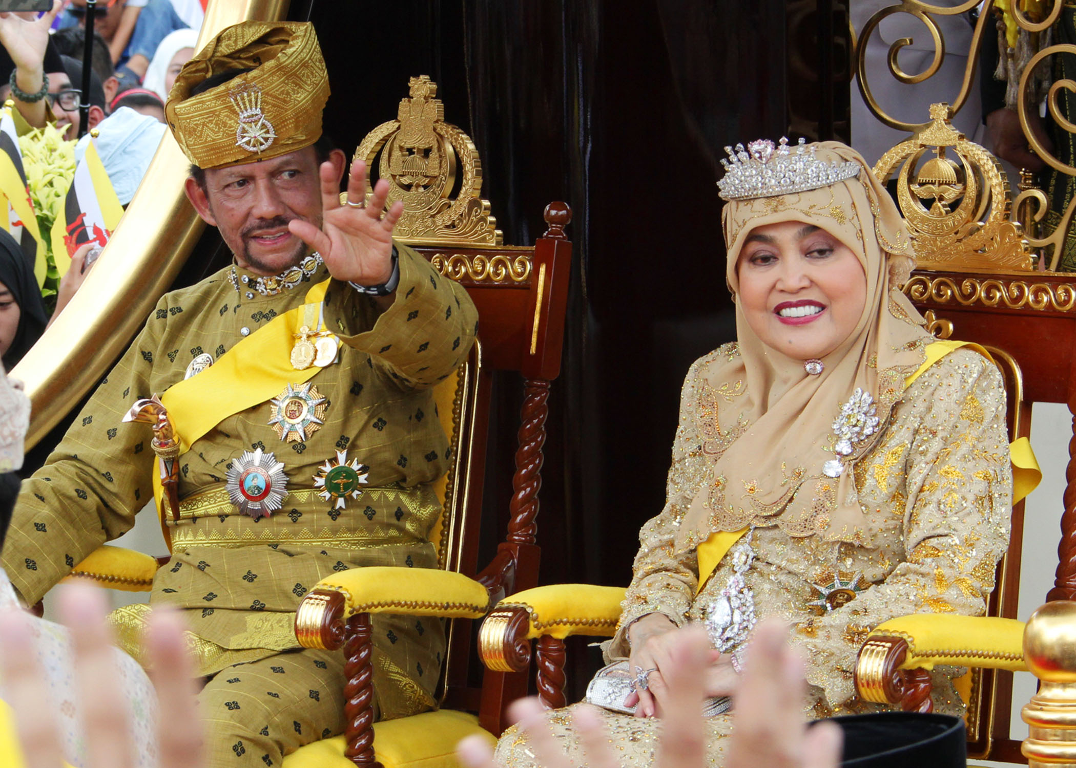 His Majesty waves to the crowd during the Golden Jubilee procession through the capital. Photo: Infofoto