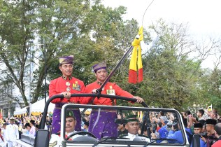 Pengarah Hj Ibrahim Hj Yussuf (R) was one of the two men tasked with guarding the 'Changkah' (huge two-pronged spear) onboard a customised vehicle which was part of the royal procession. Photo: Infofoto