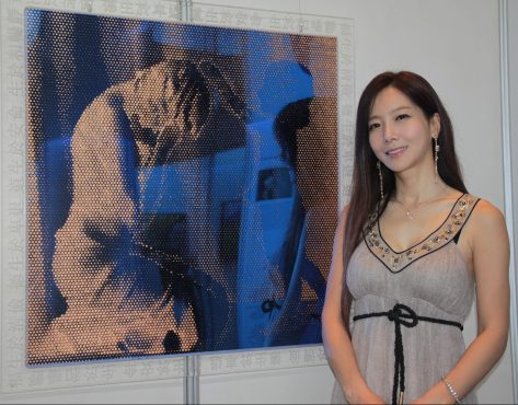 Korean artist Kim Hye Jin poses with a painting inspired by her mother. Photo: Rasidah Hj Abu Bakar/ The Scoop