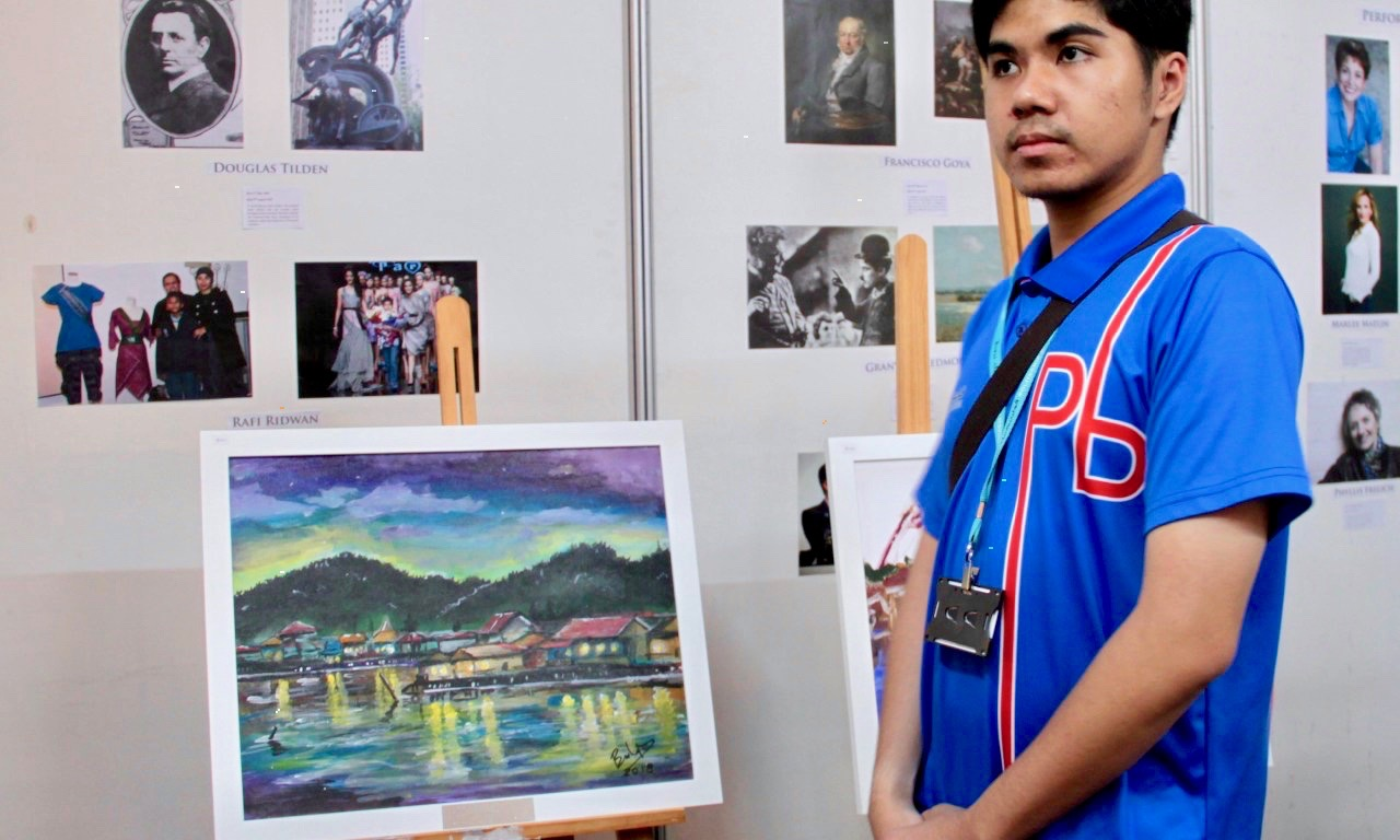 Hassan Husaini Kamar Ariffin with his painting on display at the 'Better Hearing, Better Living' art exhibition held at The Mall, Gadong. Photo: Rasidah Hj Abu Bakar/The Scoop