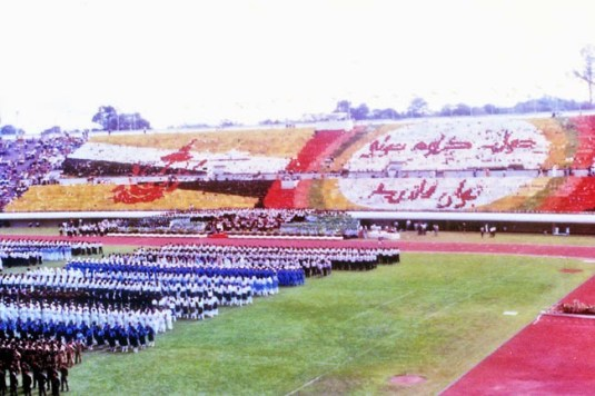 More than 10,000 students held coloured umbrellas and flip cards to display the national flag and slogan in Jawi. Photo via Brunei History Centre/Infofoto