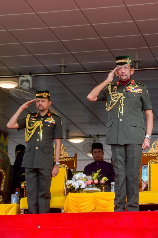 His Majesty and the Crown Prince salute during the national anthem on Brunei's 34th National Day. Photo: Infofoto