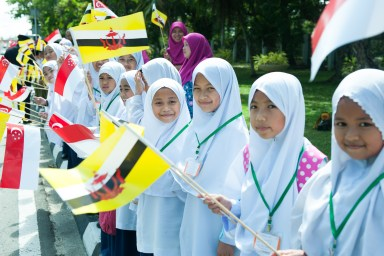 Students line the streets of the capital to welcome Singapore President Halimah Yacob. Photo: Infofoto