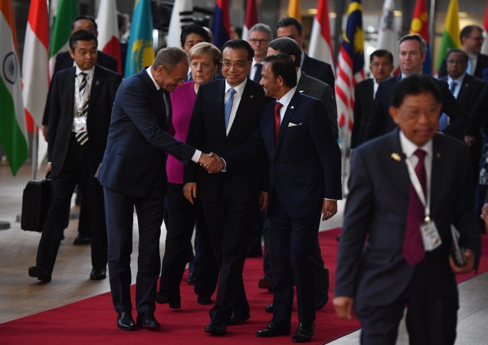 European Council President Donald Tusk (L) shakes hands with Sultan of Brunei Haji Hassanal Bolkiah (R) as China's Premier Li Keqiang (C) looks on as they walk with other leaders arriving to pose for a family photograph during an ASEM summit at the European Council in Brussels on October 19, 2018. Photo: Ben Stansall/AFP