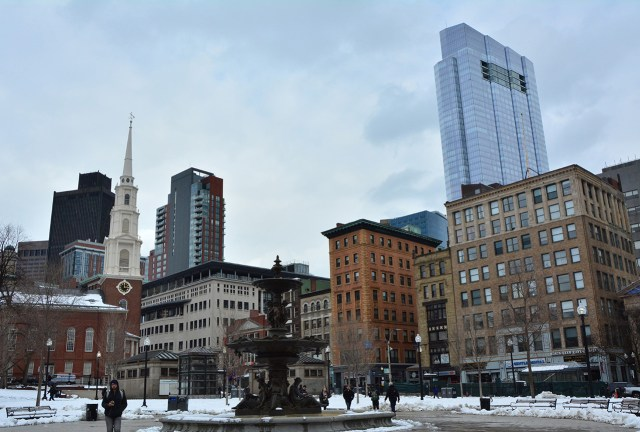 This image shows a fountain in Boston Common in the foreground, and in the background a skyline of tall buildings. The tallest and newest one stands out above the rest. It is Millennium Tower.