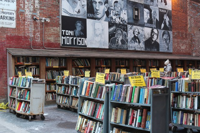 This image shows the open lot beside Brattle Book Shop which is full of carts of books. The brick wall of the book shop is painted with a mural of different authors.