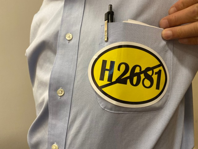 """Opponents of the bill wore yellow stickers that read """"H.2681"""" with a line through it. Photo by Alexa Gagosz."""