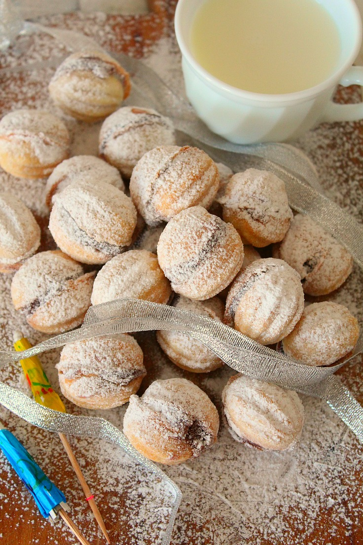 Walnut shaped cookies made with walnut cream,, next to a cup of milk
