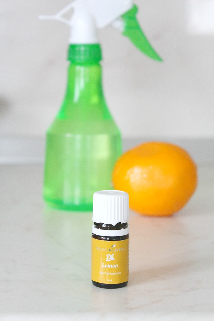 Image of lemon disinfectant in a light green spray bottle, next to a bottle of essential oils and a lemon fruit