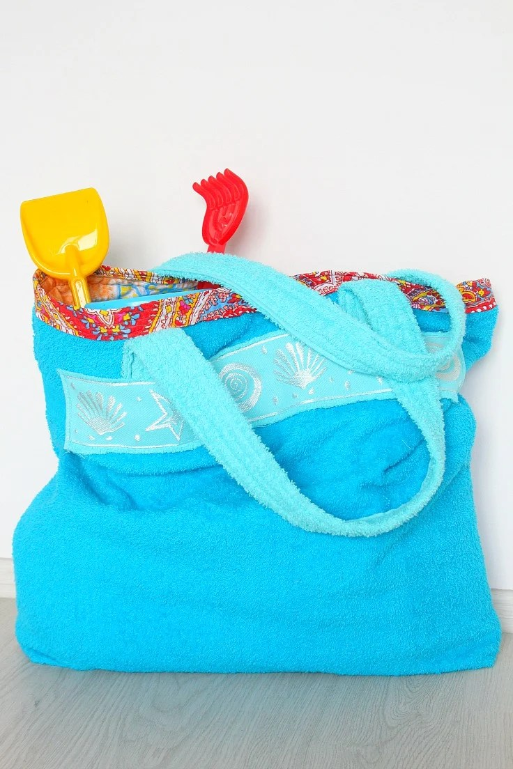 A towel bag for beach in two shades of blue, filled with beach toys for kids, sitting against a white wall.