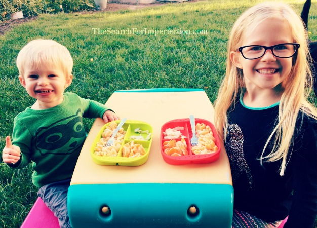Brother and sister eating together at the kids table.