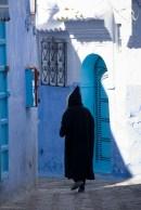 A man in a djellaba walks through light and shadow.