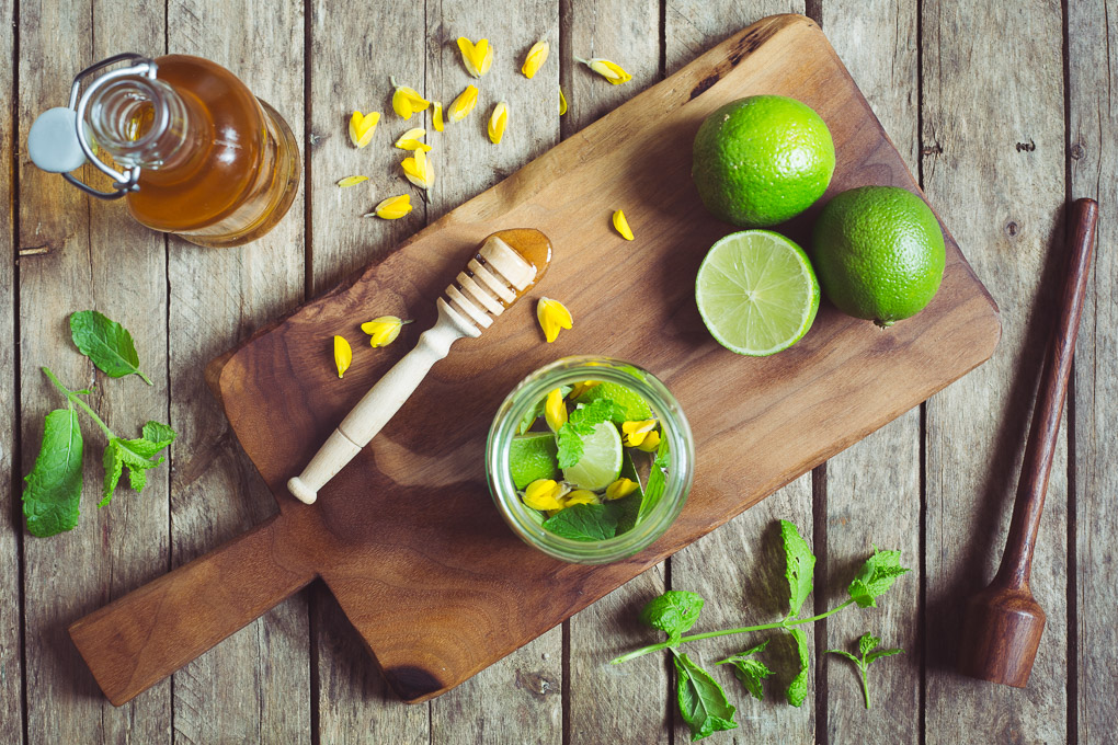 Gorse Flower and Raw Honey Mojito -- Use a muddle to gently squash the lime, mint leaves, gorse flowers (if using), and honey together in the bottom of the glass | https://theseasonaltable.co.uk/drinks/gorse-flower-and-raw-honey-mojito/
