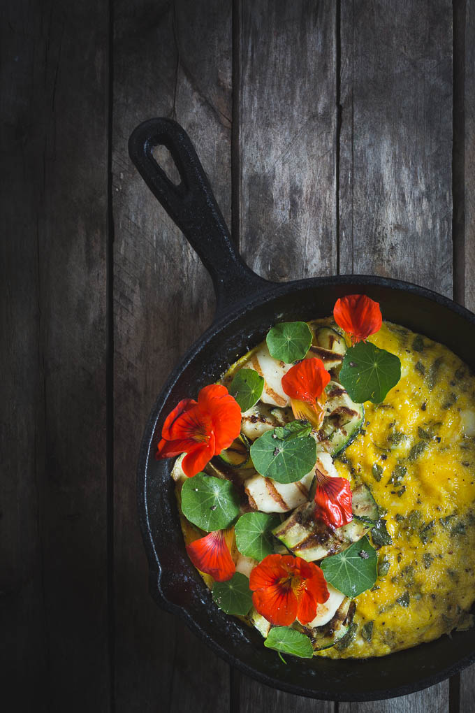 Herbed Omelette with Griddled Courgette, Halloumi, and Nasturtiums -- In a skillet   https://theseasonaltable.co.uk/brunch/herbed-omelette-with-griddled-courgette-halloumi-and-nasturtiums/