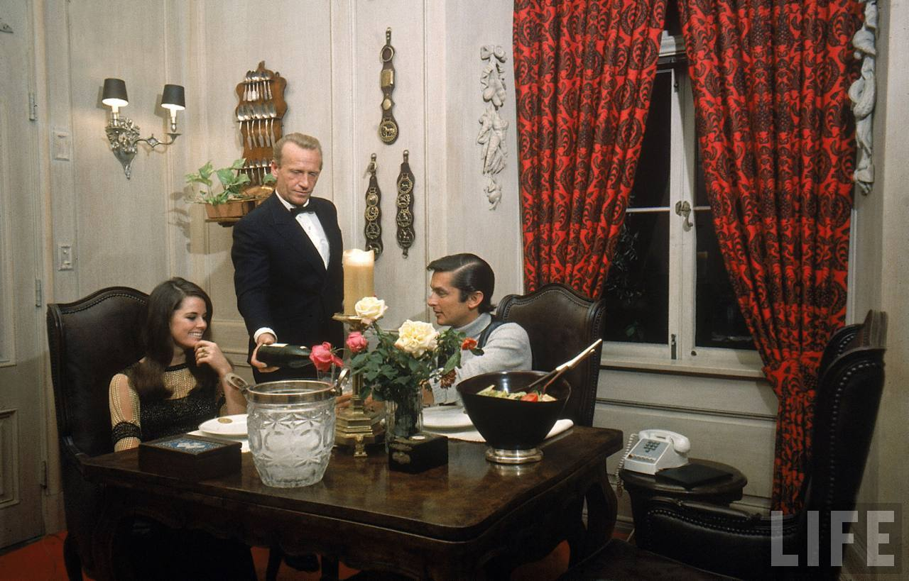 Film director Robert Evans and girlfriend Libby Boehmer being served dinner by butler at his home-- Beverly Hills, 1968.