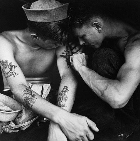 December 1944, aboard the U.S.S. , Pacific Ocean --- A sailor aboard the U.S.S.  inspects another sailor's tattoos.