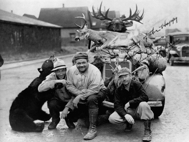 Original caption -- Baseball star Babe Ruth and fellow hunters pose in front of an automobile with the animals they captured. -- date unknown.