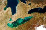 Tan fingers of sediment and green swirls of algae are visible in Lake Erie on March 21, 2012.