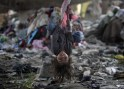 A child living in a slum plays on a swing under a bridge on the bank of Bagmati River in Kathmandu, Nepal, Oct. 17, 2011.