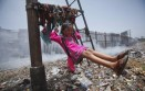 Sana, a 5-year-old girl, plays on a cloth sling hanging from a signalling pole as smoke from a garbage dump rises next to a railway track in Mumbai, India, in 2012.