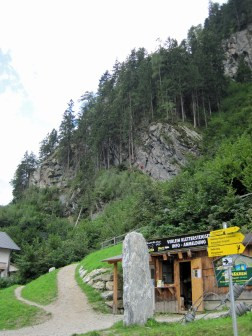 A via ferrata gear rental shop and, behind it in the trees, the Klettersteig Huterlaner.